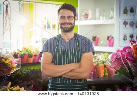 Portrait of male florist with arms crossed at his flower shop
