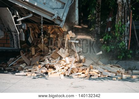truck pours out the wood on the ground, pile