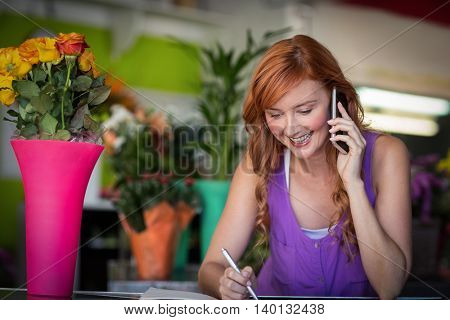 Female florist taking order on mobile phone in the flower shop