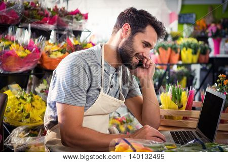 Male florist talking on mobile phone while using laptop at his flower shop