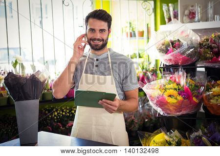 Portrait of male florist talking on mobile phone while holding file at his flower shop