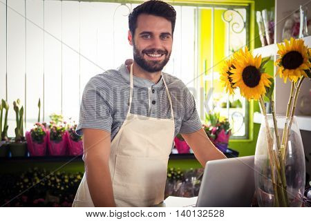 Portrait of male florist with laptop at his flower shop