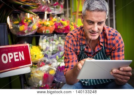 Male florist using digital tablet at his flower shop