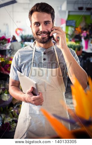 Portrait of male florist talking on mobile phone at his flower shop