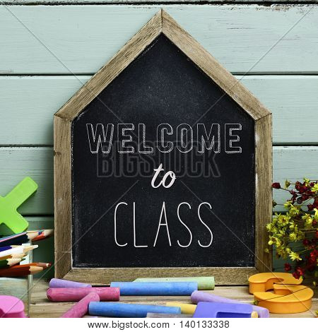 closeup of a house-shaped chalkboard with the text welcome to class written in it and a pile of pieces of chalk of different colors, against a pale green wooden background