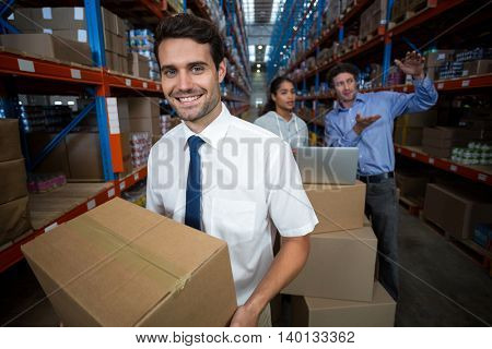 Focus of manager holding cardboard box and smiling in a warehouse