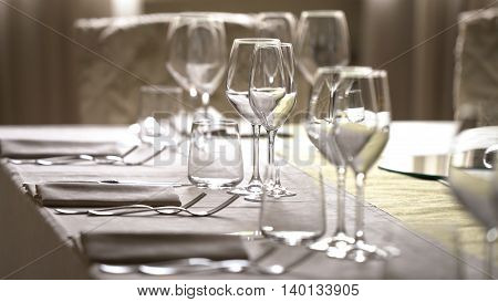 Table with white tablecloth and crystal glasses.