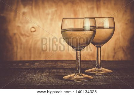 Glasses with white wine on rustic wood background, copy space, toned