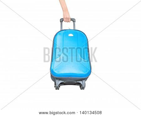 Closeup blue luggage with blurred woman hand dragging a luggage isolated on white background fabric luggage with plastic roller for travel concept