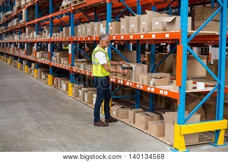 View of worker is checking cardboard boxes in a warehouse