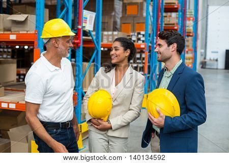 Portrait of managers with hard hat are looking each other and laughing in a warehouse