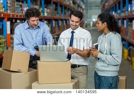 Worker team looking a laptop put on a cardboard box in a warehouse