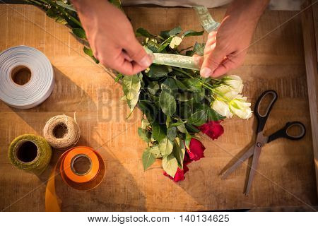 Close-up of male florist tying poly ribbon on bunch of flowers at his flower shop