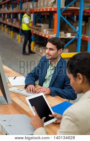 Focus on manager is working on a computer with his colleague in a warehouse