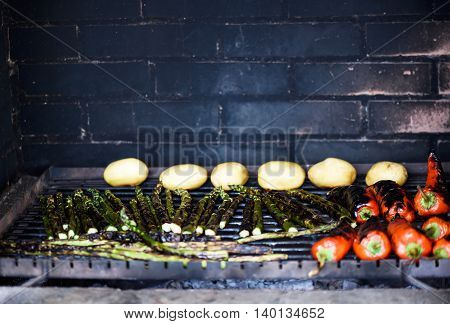 Photo of vegetables on grill pepper potatoes and asparagus shallow focus.
