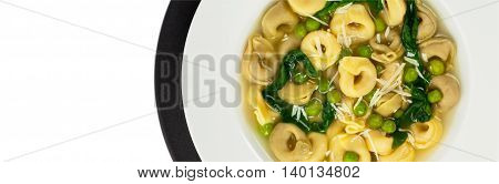 Tortellini Soup with Peas and Spinach Isolated. Selective focus.