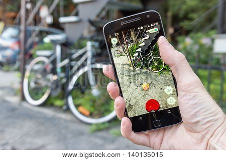 Montreal CA - July 27 2016: Closeup of a man playing Pokemon Go on a smart phone. Pokemon Go is a virtual reality game released in July 2016.