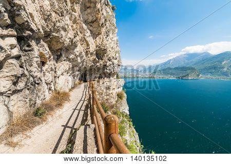 The Ponale trail carved into the rock of the mountain in Riva del Garda Italy.
