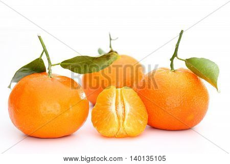 three orange clementines on a white background