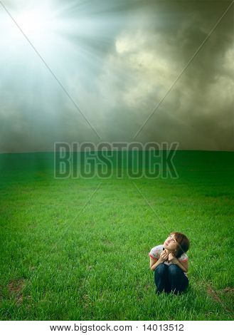 Young woman on green meadow under storm clouds