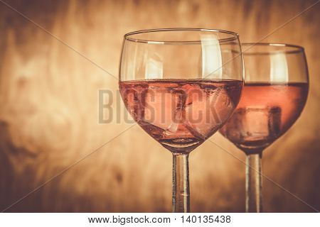 Glasses with rose wine on rustic wood background, copy space , toned
