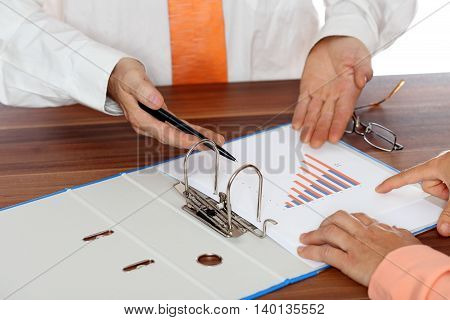 two people are working on a document in office