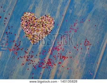 the heart is lined with colorful confetti on blue wooden boards