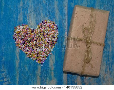 the heart is lined with colorful confetti on blue wooden boards next to her is a gift