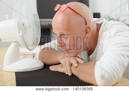 a mature man refreshed with a fan