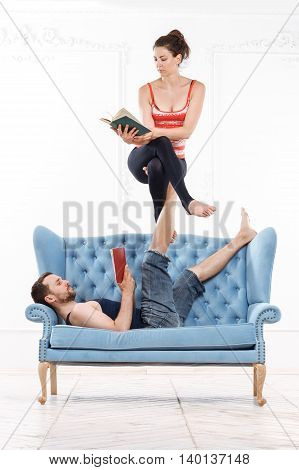 Young Beautiful Man And Woman Practicing Acroyoga On Blue Sofa Doing Excercise And Reading Books In White Interior