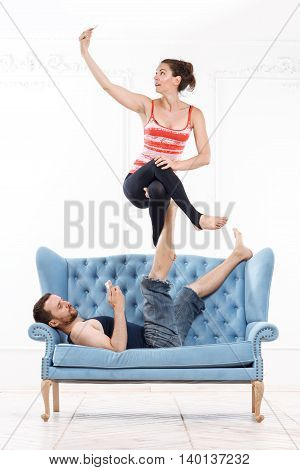 Young Beautiful Man And Woman Practicing Acroyoga On Blue Sofa Doing Excercise And Selfie In White Interior