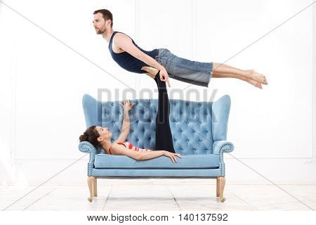 Young Beautiful Man And Woman Practicing Acroyoga Doing Excercise On Blue Sofa In White Interior