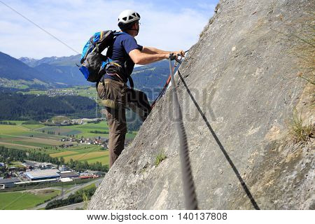 man on a rock wall in austria
