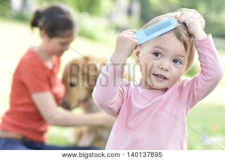 Baby girl trying to comb her hair