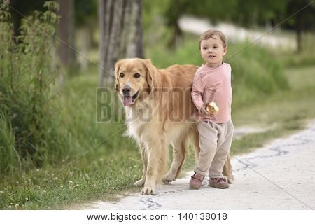 Baby girl giving a walk to dog in countryside