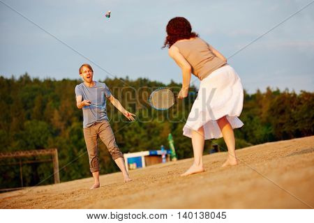 Happy couple playing badminton together at beach in summer