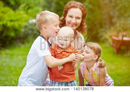 Family with baby and two children together in a garden in summer