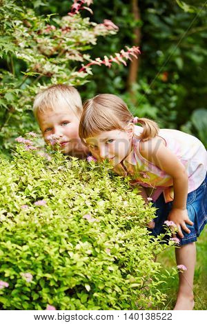 Two children playing hide and seek in garden and hiding behind a bush