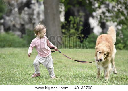 baby girl giving a walk to dog at the park