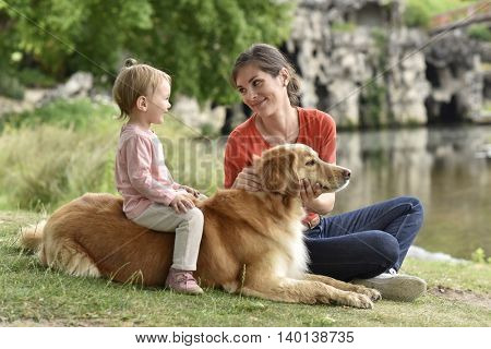 Woman and baby girl playing with golden retriever dog