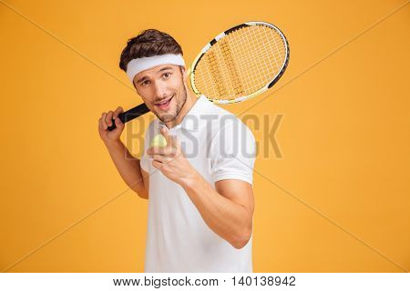 Happy attractive young man tennis player holding racket and pointing on you over yellow background