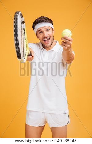 Happy young man tennis player inviting you to play over yellow background