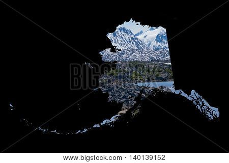 Framed in a dark black background a silhouette of Alaska is filled with a beautiful scenic image of snow covered mountains rugged terrain and a beautiful lake. Ample room for text / copy.
