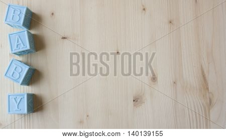 Blue Baby Blocks on a Wooden Background.