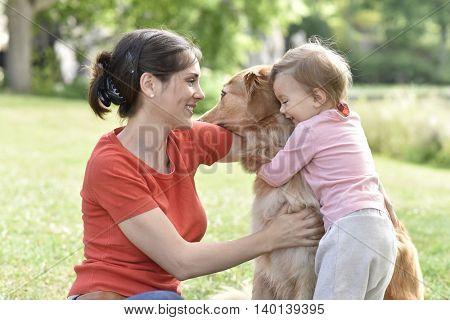 Woman and baby girl hugging golden retriever dog