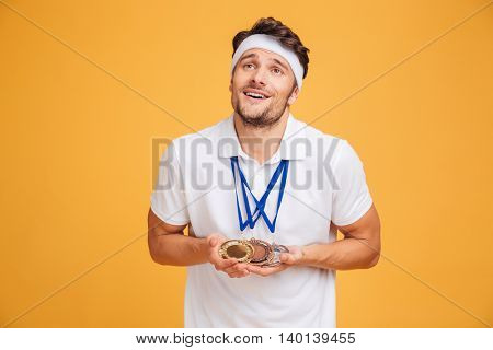Portrait of smiling young spotrsman with three medals over yellow background