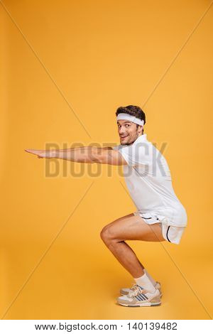 Smiling young man athlete doing exercises and working out over yellow background