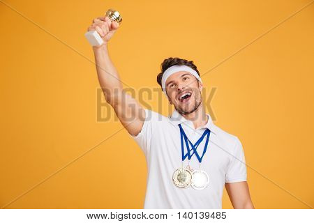 Happy young man athlete with three medals and trophy cup celebrating victory over yellow background