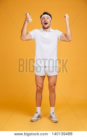 Cheerful excited young man athlete with trophy cup standing and shouting over yellow background