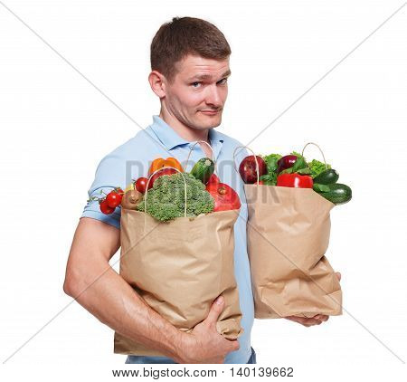 Handsome young man holding shopping bags full of groceries isolated at white background. Healthy food shopping. Paper package with vegetables and fruits, happy male buyer came from market